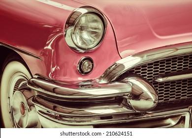 Retro gestileerd beeld van een voorzijde van een roze klassieke auto