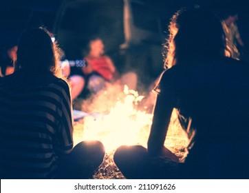 明るいたき火の周りに人々が夜に座ります