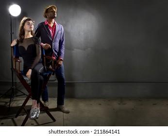 華やかな表情で具体的な背景にポーズをとるスタイリッシュな俳優