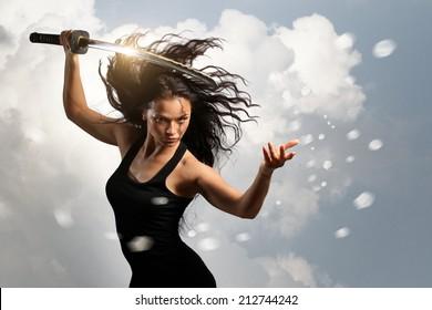Schöne aggressive Brünette, die Katana-Schwert mit trüber Umgebung hält