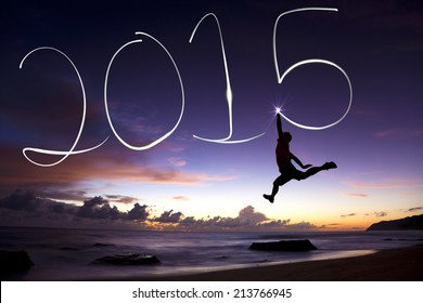 Frohes neues Jahr 2015. Junger Mann springt und zeichnet 2015 mit der Taschenlampe