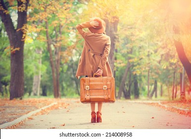 Chica pelirroja con maleta en el parque de otoño.
