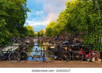 Bicicletas estacionadas a lo largo de un puente sobre los canales de Amsterdam, Países Bajos