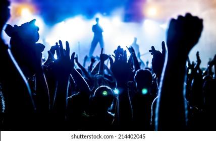 Silhouetten der Konzertmenge vor hellen Bühnenlichtern
