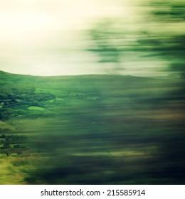 動く車の窓からの漠然とした眺め-ビンテージフィルター。車のフロントガラスを通して見た焦点がぼけた木。高速での車からのぼやけたアクション。リングオブケリー、アイルランド。