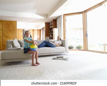 ラップトップコンピューターを持つ母親がソファーに座っている女の子(8-10)、肖像画