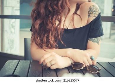 バーで赤い巻き毛の若い美しい流行に敏感な女性