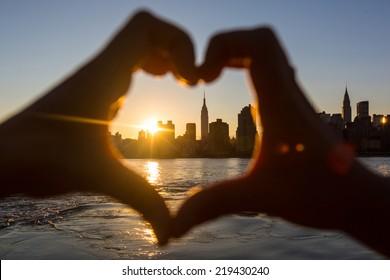 日没時のハート型の手、背景にニューヨークのスカイライン
