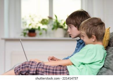 Dos jóvenes, o hermanos, sentados en un sofá jugando en una computadora portátil, vista lateral delante de una ventana