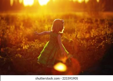 日当たりの良い夏の夜にウサギを追いかけている緑のドレスを着たかわいい女の子。子供たちが遊んでいます