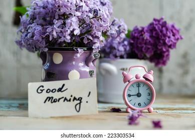 Zweifarbige Fliederblumen in einem weißen und violetten Keramiktopf, mit einem rosa Vintage-Wecker und einer Guten-Morgen-Note auf einer schäbigen Holzoberfläche
