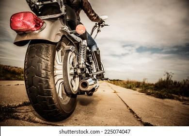 Chica ciclista montando en una motocicleta. Vista inferior de las piernas en botas de cuero. Concéntrese en la rueda trasera.