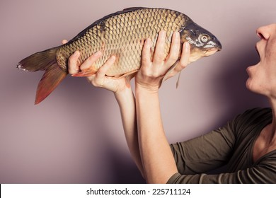 A young woman is posing with carp and is pulling silly faces
