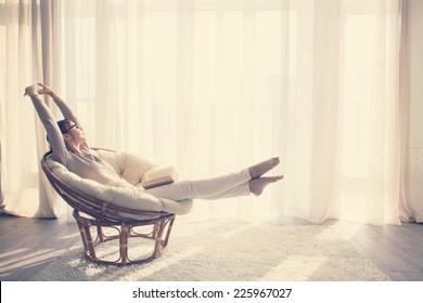 Mujer joven en casa sentado en una silla moderna frente a la ventana de relax en su sala de lectura, libro, tonificación de instagram