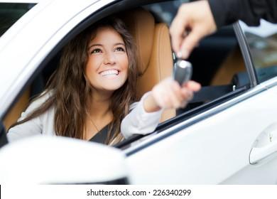 彼女の新しい車の鍵を受け取る若い女性