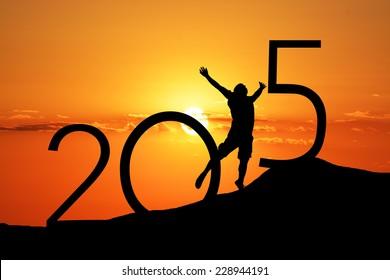 Schattenbildperson, die über 2015 auf dem Hügel bei Sonnenuntergang springt