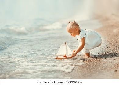 暖かい晴れた夏の日にビーチでおもちゃの船で遊んでいる白い服を着たかわいい女の子。海での休日。面白い子供たち