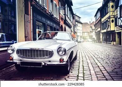 古いヨーロッパの都市通りにレトロな車を駐車