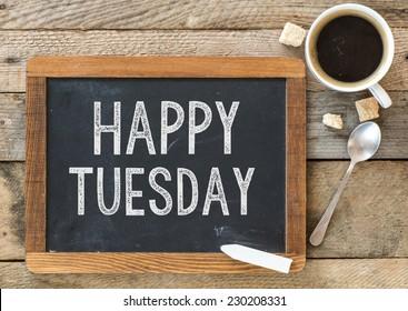 Schönen Dienstag Zeichen an der Tafel. Tafel mit Happy Tuesday-Zeichen und Tasse Kaffee auf hölzernem Hintergrund