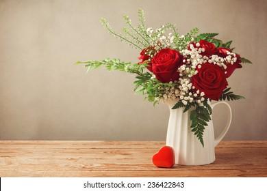 コピースペースを持つ木製のテーブルにバラの花束とハートボックス