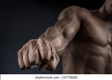 Primer plano del puño de un hombre. Mano de hombre fuerte y poderosa con músculos y venas. Estudio de rodaje. Mano del hombre