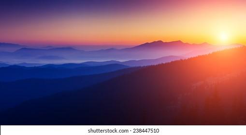Majestic sunset in the mountains landscape with sunny beams. Dramatic scene. Carpathian, Ukraine, Europe. Beauty world. Retro style, vintage filter. Instagram toning effect.