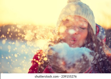 Schönheits-Wintermädchen, das Schnee im frostigen Winterpark bläst. Draußen. Fliegende Schneeflocken. Sonniger Tag. Von hinten beleuchtet. Freudige Schönheit junge Frau, die Spaß im Winterpark hat. Defokussiert