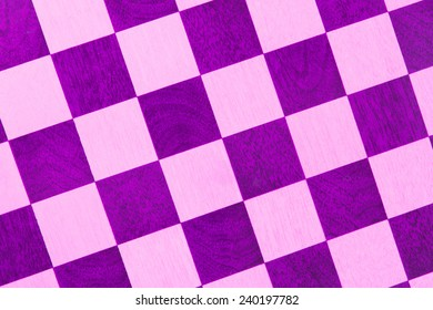 Very old wooden chess board, isolated close-up, purple