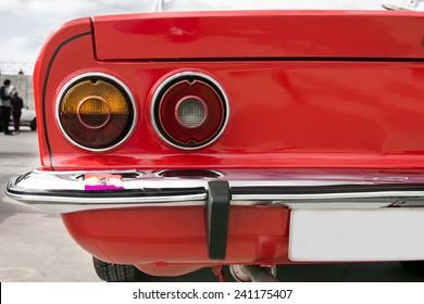Close-up van de achterlichten van een rode klassieke auto.