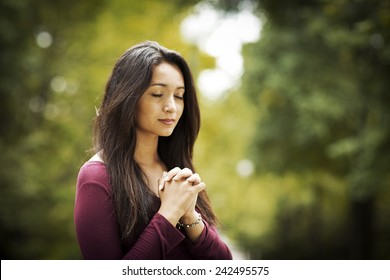 Woman hands praying in the forest. Outdoors. Nature.