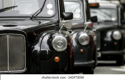 three London vintage cabs waiting in the street