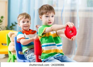Kinder Jungen reiten auf Wagen aus Stühlen