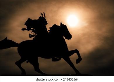 Schwarzweiss-Silhouette eines Samurai zu Pferd.