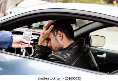 Trinken und Fahren stürzte der Fahrer ab, weil er mit einem Alkoholtester auf Alkoholgehalt getestet wurde. er ist am Boden zerstört