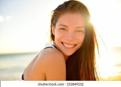 Hermosa chica asiática sonriendo feliz en vacaciones en la playa disfrutando de un cálido sol. Raza mixta asiática caucásica bastante modelo exterior con sol de fondo en la playa tropical de Hawai.