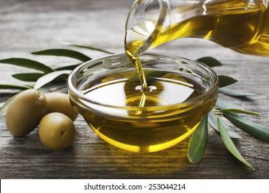 Botella vertiendo aceite de oliva virgen en un recipiente de cerca