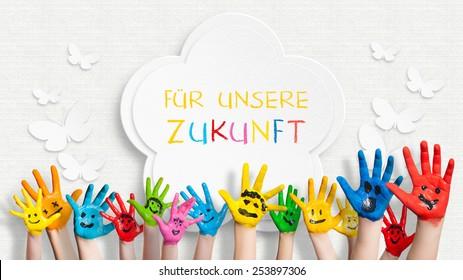 """bunt bemalte Hände vor einer verzierten Wand mit dem Satz """"Für unsere Zukunft"""" auf Deutsch"""