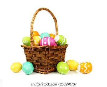 白い背景の上のカラフルな卵でいっぱいのイースターバスケット