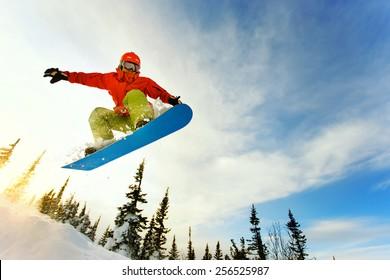 Snowboarder saltando por el aire con cielo azul profundo en segundo plano.