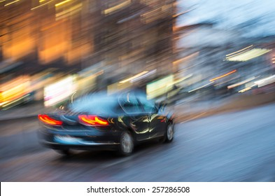 夕方の街の通りを運転するぼやけた黒い車