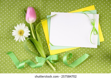 Frühlingsrahmen für Ihre Grußkarte mit Blumen und Bändern in Grün, Gelb und Rosa