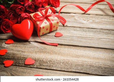 ギフト用の箱と木製の背景に赤いハートのバラの花束