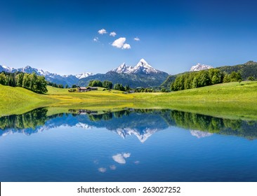 Panoramablick auf die idyllische Sommerlandschaft in den Alpen mit klarem Bergsee und frischen grünen Bergwiesen im Hintergrund