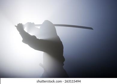 Ein echter Ninja schoss auf einen mit Rauch gefüllten Raum und Blitzlicht, um einen dramatischen Effekt zu erzielen.