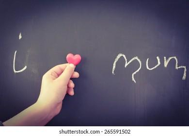 Ich liebe Mama, die auf eine Tafel geschrieben ist, mit einer Kinderhand, die ein Liebesherz hält