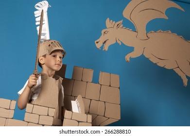 foto del niño en traje de caballero medieval hecho de cartones