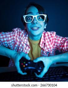Le gusta jugar y ganar videojuegos. En la luz azul del monitor, el niño emocional juega juegos de computadora en línea.