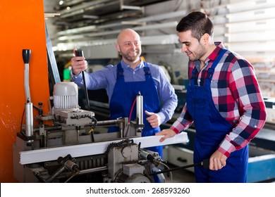 Trabajadores cortando perfiles de aluminio en una instalación de producción de ventanas