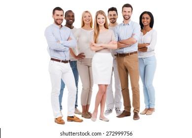 Stolz ein Team zu sein. Volle Länge der multiethnischen Gruppe von Leuten in der intelligenten Freizeitkleidung, die Kamera betrachtet und lächelt, während sie gegen weißen Hintergrund steht