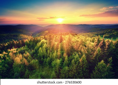 Vogelperspektive eines malerischen Sonnenuntergangs über den Waldhügeln, mit getönten dramatischen Farben